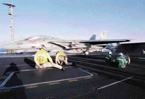Young crewmembers on a U.S. Navy aircraft carrier coordinate complex systems in a dangerous situation, but thanks to very closeteamwork mistakes are rare.