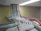 A typical dense mass of cables running from a telecommunications closet through a cable tray before entering the plenum space.