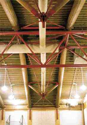 Gymnasium roof truss with simple pipe connectors at far wall.