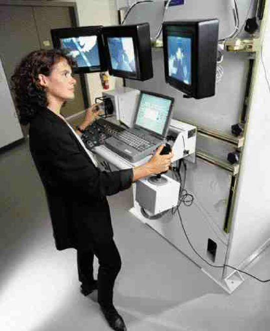 Left: Canadian astronaut Julie Payette testing a training module on a robotic work station at the Canadian Space Agency.