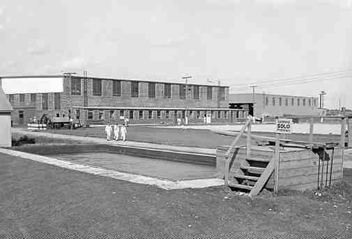 The No. 2 Hangar at Oshawa, Ontario, circa 1943. In the foreground is a swimming pool-cum-water reservoir for firefighting. Many of the airfields remain in use today, and in 1999 this was the first to be commemorated as a National Historic Engineering Project.