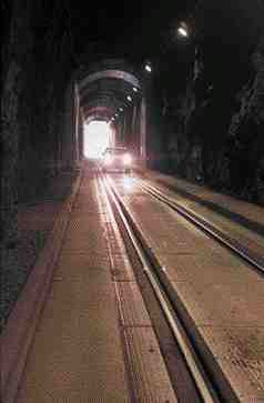 Car proceeds through the longest highway tunnel in North America. The road surface is precast concrete panels with embedded tracks.