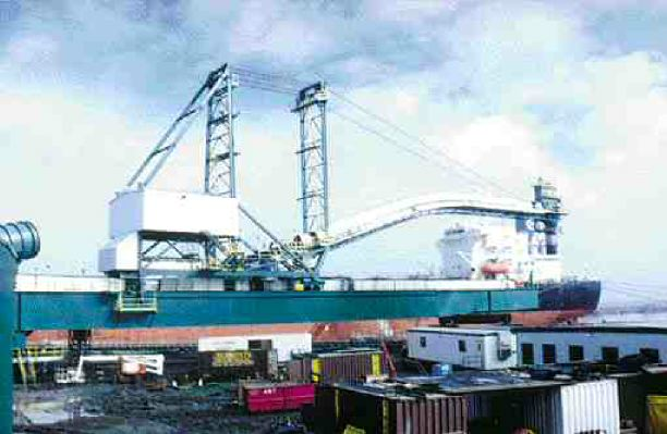 Loading a vessel. The huge machinery operates at various speeds, pivoting, dipping and rising, and extending to a full length of 125 metres.