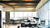 Second floor office interior, with exposed wood ceiling and floor made from salvaged decking and glulam.