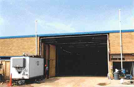 """Water treatment trailer at left of door opening, """"bioslurping"""" vacuum extraction unit at right."""