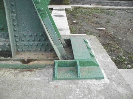 Baseplate that is allowed to uplift several inches during an earthquake. Nuts were removed from the anchor bolts and guides were installed to prevent lateral movement.