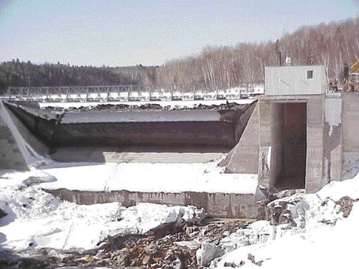 The original stoplog bays were replaced by a concrete ogee spillway, topped with a five-metre high rubber dam. A submerged gate allows operators to draw the reservoir below the ogee crest and a control system allows deflation in response to rising water levels. In winter and early spring rapid ice jam break-ups have historically caused flooding problems at the site.