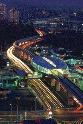 """Station illuminated at night, showing the curved timber roof split by a """"zipper"""" along the centre and with open glass walls all around."""
