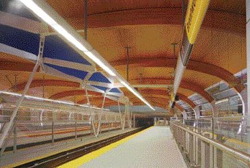 """Station interior. The wooden roof shell is supported on glue-laminated timber ribs and steel """"haunches."""" The ribs all have an identical inside curved shape to make manufacturing them more efficient."""