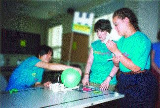 """Students prepare to launch their """"jet propulsion"""" vehicle down the course."""