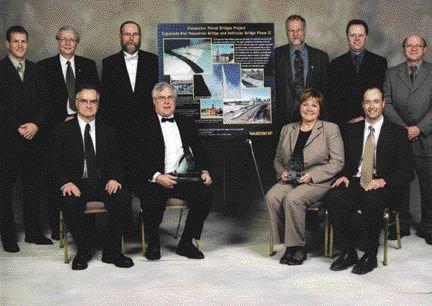 AWARD OF EXCELLENCE. Esplanade Riel, Winnipeg. Wardrop Engineering. Left to right, standing: Dave Bowen, Garry Bolton (ACEC), Fred Corey (City of Winnipeg), Bob Kurylko, Rick Haldane-Wilsone, Bill Larkin (City of Winnipeg). Seated: Bill Ebenspanger (City of Winnipeg), Doug Stewart, Annitta Stenning (City of Winnipeg), Robert van Ginkel.