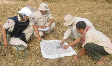 Local trainees and staff confer over maps. Satellite imagery, followed by GPS surveying, helped identify uncultivated, landmined areas which could then be cleared and allocated to owners; over 3,700 property titles were created, with very few disputes.