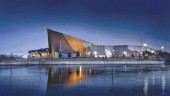 """museum viewed from Victoria Island at night. The building is low and broad and rises to face east with a 24-metre high, triangular """"fin."""""""