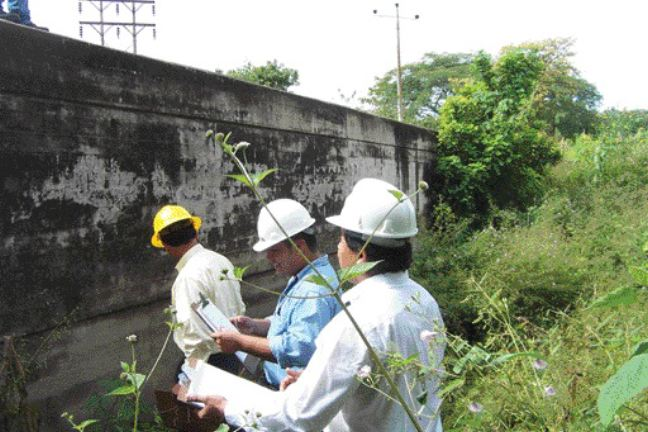 inspecting the Wing Wall Dam at Guajoyo, El Salvador.