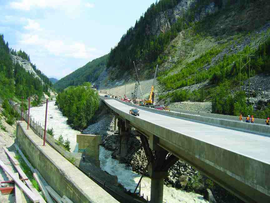 New four-lane highway nearing completion; a special drainage system includes large scuppers in the parapet.
