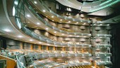 Inside the auditorium where column-free balconies, lit by LEDs, wrap tightly around the stage. Every geometry and surface is designed to support the sound.