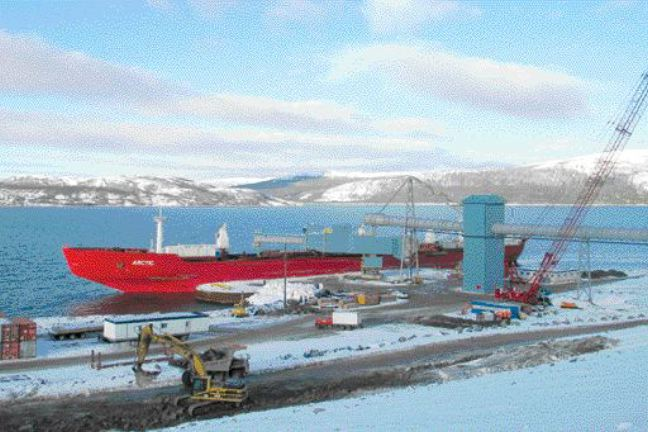 Loading nickel concentrate onto the icebreaker MV Arctic at the wharf; the shiploader is supported within one of the four circular sheet pile structures that make up the wharf.