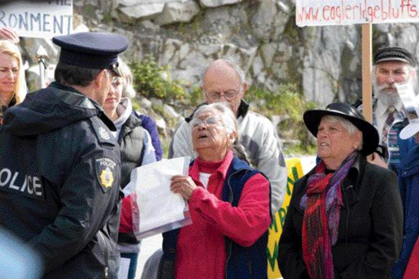 Protestors from the Coalition to Save Eagleridge Bluffs being arrested last May in B.C. The group objects to a new stretch of the Sea-to-Sky highway being constructed near Lions Bay. Photograph by Christopher Grabowski.
