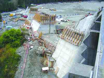 Early construction of the gravity wall extension that retains the new earth fill dam.