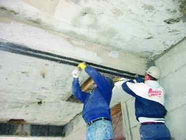 Workers reinforce beams using fibre composite materials.
