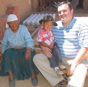Petrucci in Villa Rivero, Bolivia, with young Miguel and his grandmother Alehandrina. The construction materials are for new sanitation facilities.