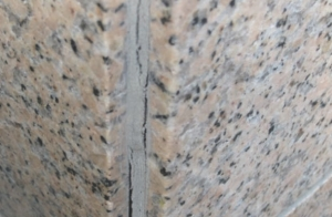 20-year old polyurethane sealant that has failed adhesively at bottom left edge and middle right edge; sealant has failed cohesively at top.
