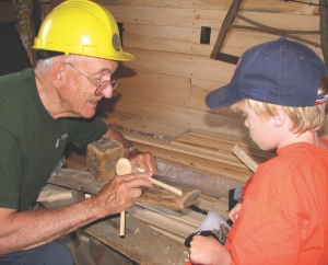 Rehder demonstrating woodworking tools to a young visitor in the restored mill's museum.