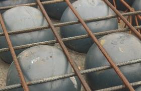 Recycled plastic spheres in reinforcing grid.