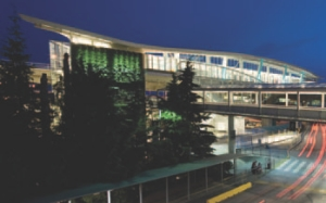 Canada Line terminus at YVR-Airport Station. The station sits 18 metres high straddling a road and has a large green wall covering its north side.