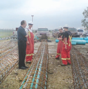 Preparing rebar for the 20-m deep piles; the geothermal pipe loops are attached inside.