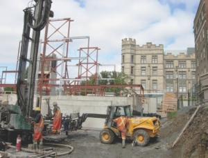 Drilling boreholes 137 metres deep throught bedrock for the geoexchange system. In the background is the Victoria Memorial Museum Building.