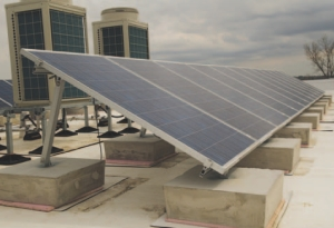 A 5.5 PV system sits in front of rooftop heat pumps; the pumps connect to fancoil units in a variable refrigerant flow heating/cooling system.