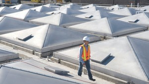 An engineer walks between the odour control covers on the primary clarifiers.