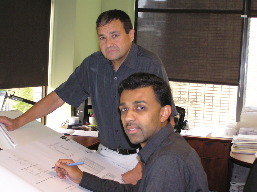 """Met Ulker and Sunny  Ghataurah of Applied Engineering Solutions look over plans in the Vancouver office. Ulker, a senior partner, and Ghataurah, a younger partner, are symbolic of the gap in engineering that is occurring as the middle-aged engineer is almost non-existent. For individuals like Ghataurah, it is a fantastic opportunity """"to drive the bus"""" and take a leadership role in the firm.  Photo by Jean Sorensen"""