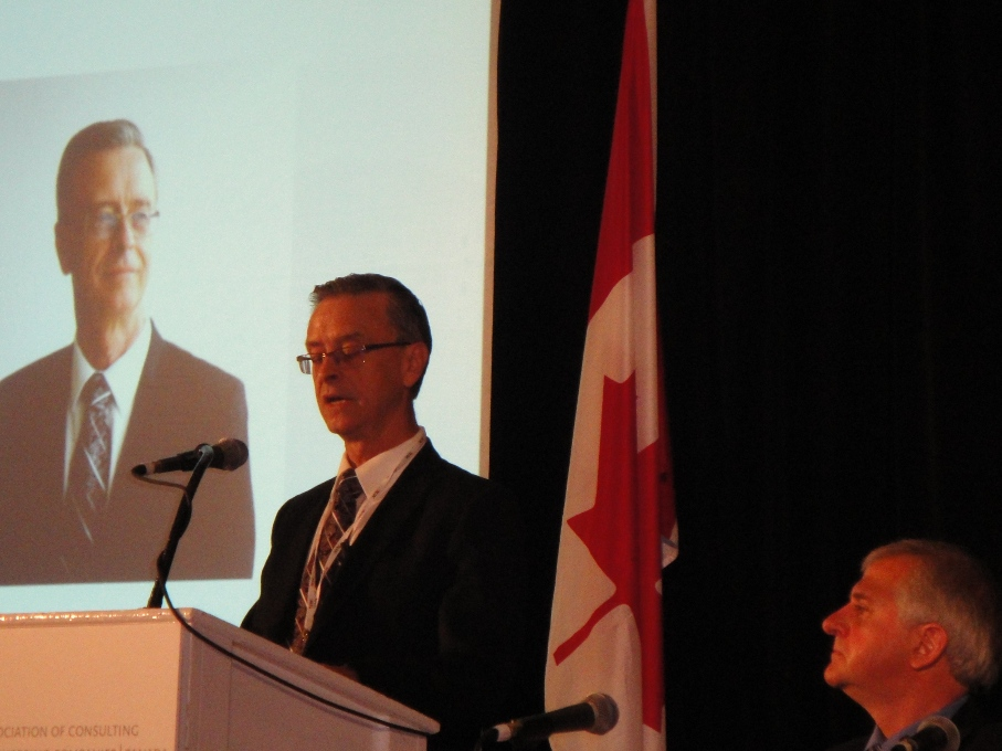 Murray Thompson, incoming chair of ACEC-Canada speaks at the annual summit in P.E.I. (left).  Outgoing chair Herb Kuehne is at right.