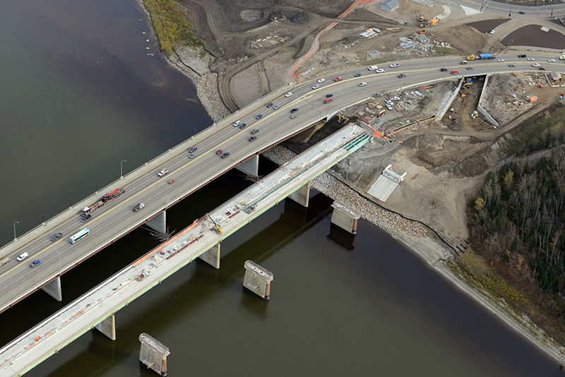 Bridges over the Athabasca River in Fort McMurray, Alberta. The Athabasca River Bridge is completed on the left, the Steinhauer Bridge is shown under construction in the middle. On the right are the piers that were re-used for the new Grant MacEwan Bridge that was just opened. Photograph courtesy Alberta Transportation.